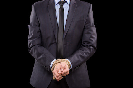 Man in suit with hands tied in criminal trial